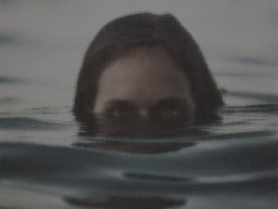 A head of a man or woman half-submerged in lake water. An art teacher, who appears in a short story called Lake Forever by Maureen Paxton